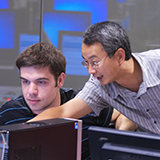 Kevin Du gestures toward a computer screen in a computer science classroom.