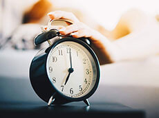 A person reaching over to shut of an alarm clock.