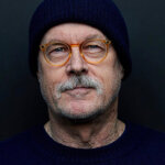 Photo of Mark Tinker wearing a blue beanie and glasses