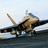 A fighter jet landing on an aircraft carrier